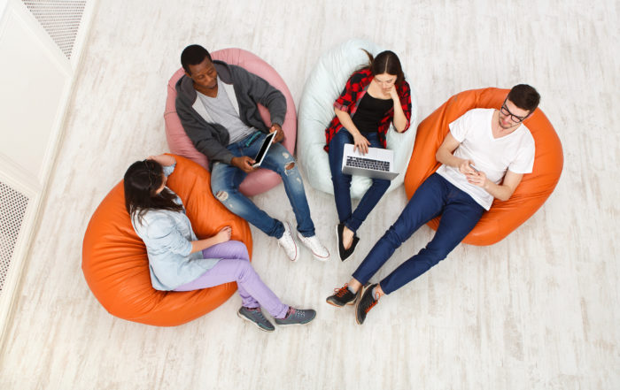Diverse youth sitting on chairs talking